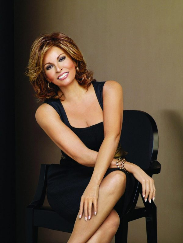 Raquel Welch in black dress and chair with Embrace Wig